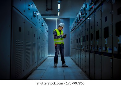 The engineer checking and inspecting at MDB panel .he working with electric switchboard to check range of voltage working in Main Distribution Boards factory.