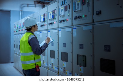 Engineer checking and inspecting at MDB panel .he working with electric switchboard to check range of voltage working in Main Distribution Boards factory.