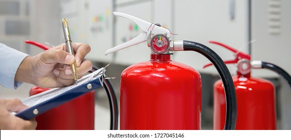 Engineer are checking and inspection a fire extinguishers tank in the fire control room for safety training and fire prevention.