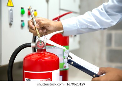Engineer are checking and inspection a red fire extinguishers in the fire control room for safety prevention and fire training.