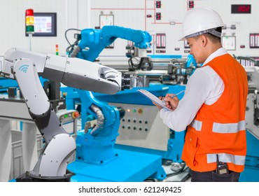 Engineer checking maintenance daily of automated robotic in production line, Industry 4.0 concept