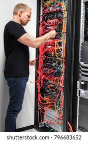 IT Engineer Checking With Network Cables Connected To Servers