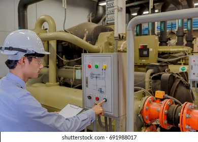 Engineer checking operating Industrial Chillers, hot water pump and pipe line for make high temperature condition in HVAC systems.