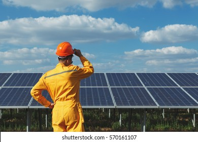 Engineer checking the solar panel. with blue sky and Cloud background. His hands grip helmet at the solar panel