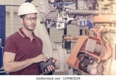 engineer checks the connectivity of some robots in a car production plant. the assembly line has to be interrupted during maintenance
