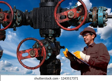 Engineer with clipboard inspecting oil field equipment low angle shot