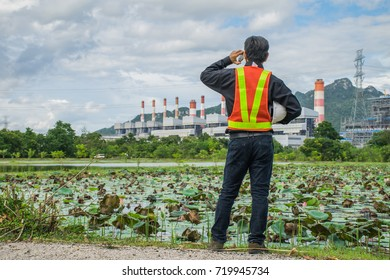 Engineer with a coal power plant in the background, Thailand.