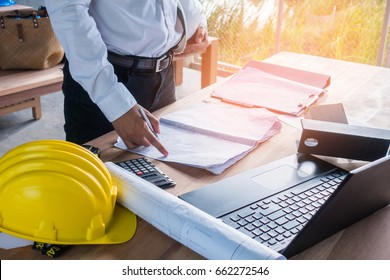 Engineer concept : Architect working on blueprint.engineer inspective in workplace , laptop ,calculator, blueprints,helmet. Vintage filter effect