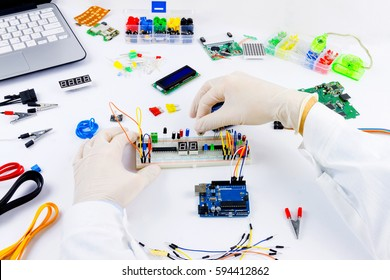 Engineer is connecting microchip to microcontroller mannually. Microcontrollers, chips, resistors and light-emitting diodes on white desktop of hardware engineer