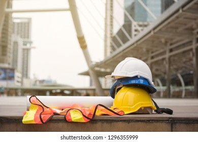 Engineer and construction equipment with copy space for text. Safety helmet hats, blueprint paper project, and worker dress on concrete floor at modern city with blurred people.