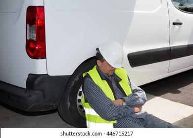 Engineer in construction sleeping beside his car