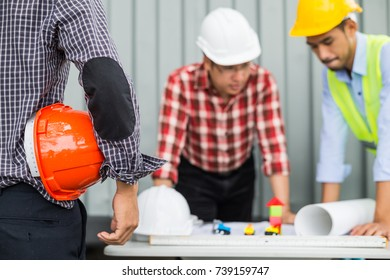engineer and construction team wearing safety helmet and working by checking progress of construction in blueprint, reviewing material and checking construction process at construction site area.