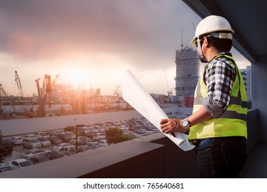Engineer consult people holding blueprint in his hand and thinking about construction planning in the future.