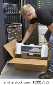 It engineer / consultant install / unpack a server or a network router / switch in a data center.
