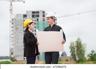 Engineer contractor reading drawing building with under construction building background.