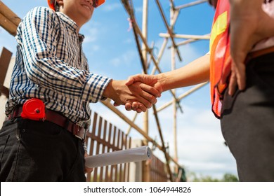 Engineer contractor shaking hands at break down house construction site working architecture planning in sunny weather day.
