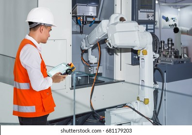 Engineer controlling automatic robotic hand machine tool with CNC machine in automotive industry