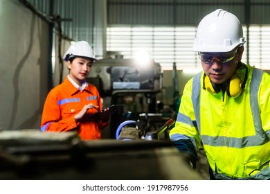 engineer cooperation Two asian maintenance engineers men and women inspect relay protection system with tablet device to control quality control process work a heavy industry manufacturing factory