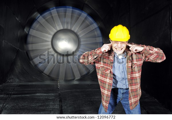 An engineer, covering his ears to protect them from the noise of a wind tunnel being tested