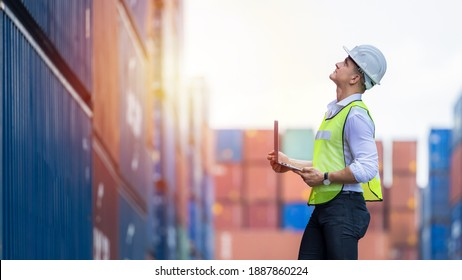 Engineer dock worker wear safety uniform check control loading freight cargo container use computer laptop at commercial dock warehouse, Global business logistic transportation cargo freight shipping. - Shutterstock ID 1887860224