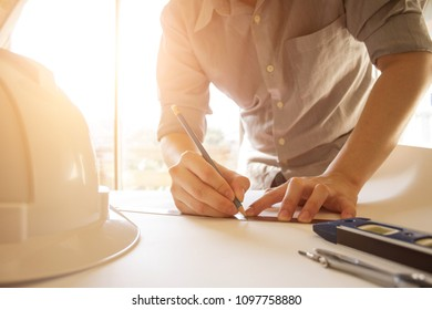 engineer drawing and planning architectural project with engineering tools on desk in office