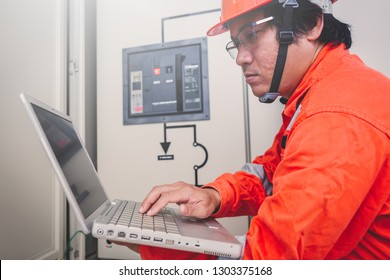 engineer or electrician holding laptop for inspect and checking main distribution board by wifi technology ;smart technology for operation of solar power plant by smart operator