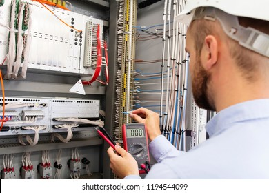 Engineer electrician with multimeter in electrical control box tests equipment. Maintenance of electrical panel. Worker in helmet in power supply cabinet. Service man is testing automation fuse box.