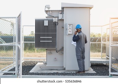 engineer or electrician working on checking and maintenance equipment at green energy solar power plant ; checking status step up transformer high voltage at transformer yard and talking phone