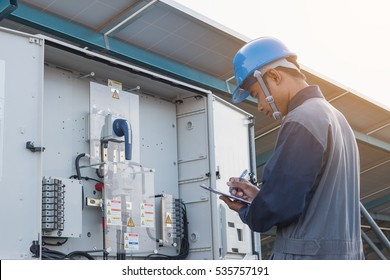 engineer or electrician working on checking and maintenance equipment at green energy solar power plant: checking status inverter
