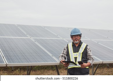 engineer or electrician working on  maintenance equipment at industry solar power; engineer charging his phone by small solar panel charger at solar power plant