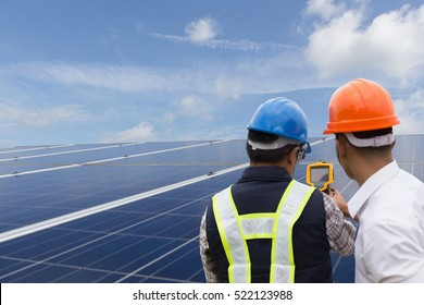engineer or electrician working on maintenance equipment at industry solar power; engineer using IR camera to check temperature heat of solar panel