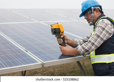 engineer or electrician working on  maintenance equipment at industry solar power;  engineer using thermal imager to check temperature heat of solar panel
