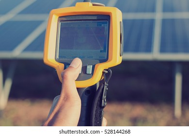 engineer or electrician working on  maintenance equipment at solar power plant;  engineer using thermal imager to check temperature heat of solar panel
