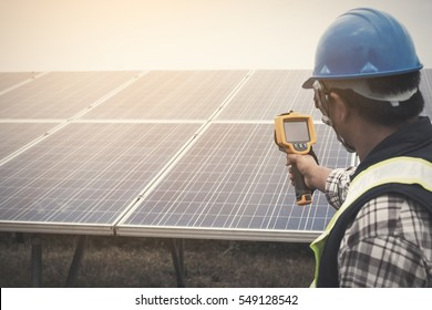 engineer or electrician working on  maintenance equipment at industry solar power; engineer charging his phone with small solar cell at solar power plant