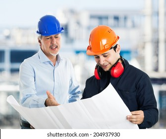 Engineer explaining a drawing to a worker