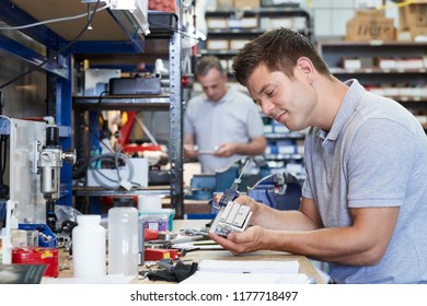 Engineer In Factory Measuring Component At Work Bench Using Micrometer