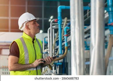engineer in factory working to check boiler water pipe in factory hand holding tablet