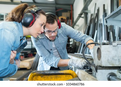 engineer and female apprentice working on machine in factory