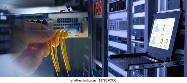 engineer and fiber optic cable on network router switch and monitor show graph information in background in technology data center room. widescreen