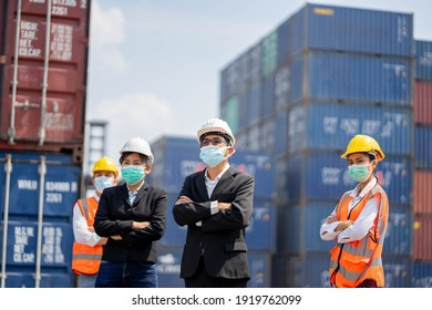 Engineer and Foreman control loading container at commercial dock cargo freight shipping, workers or engineers wearing Coronavirus or COVID-19 protective masks stand in front of the shipping container