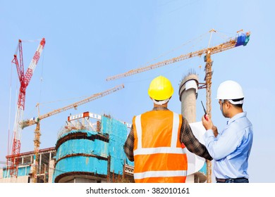 Engineer and Foreman control working at high building under construction site