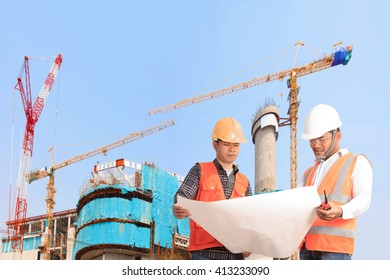Engineer and Foreman looking plan for work high building under construction site