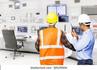 Engineer and foreman use radio communication for command working at control room of a modern thermal power plant