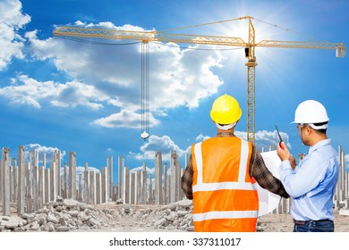 Engineer and Foreman working at building under construction with precast concrete piles with yellow construction crane tower