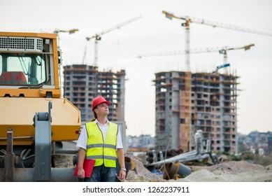 Engineer in front of excavator on a construction site with buildings and cranes in the background