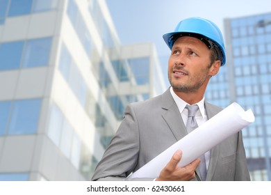 Engineer in front of modern building with plan