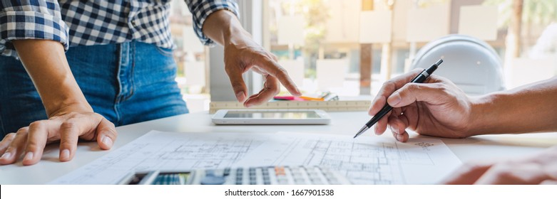engineer Hand Drawing Plan On Blue Print with architect equipment discussing the floor plans over blueprint architectural plans at table in a modern office