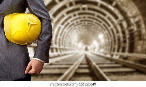 engineer hand holding yellow helmet for workers security against the background of an underground mine with arc legs and rails for trolleys with coal in perspective