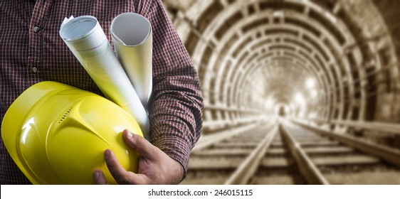 engineer hand holding yellow helmet for workers security and blueprint paper plan against the background of an underground mine with arc legs and rails for trolleys with coal in perspective