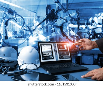 Engineer hand using computer  machine real time monitoring system software.digital manufacturing operation. Automation robot arm machine in smart factory automotive industrial , Industry 4.0 concept